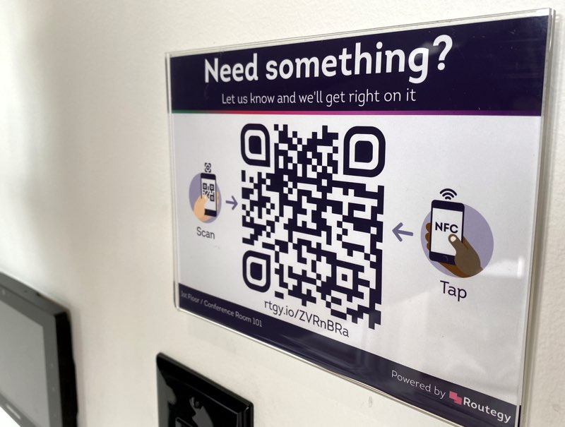 A QR code and NFC tag are mounted to a wall, prompting visitors to interact via their phone to make requests