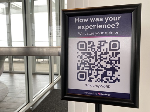 A sign in a doorway asking for customer feedback with a QR code